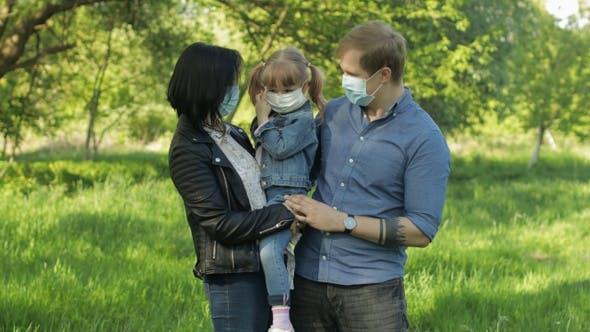 Familie im Park nimmt medizinische Masken ab, nachdem Coronavirus Pandemie Quarantäne Ende