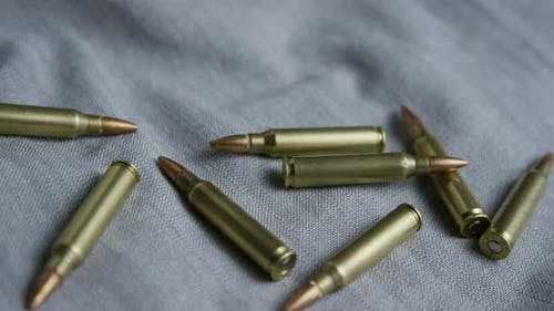 Cinematic rotating shot of bullets on a fabric surface - BULLETS