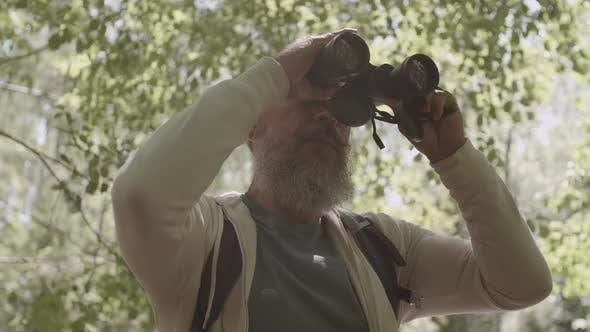 Thumbnail for Aged Traveler Using Binoculars