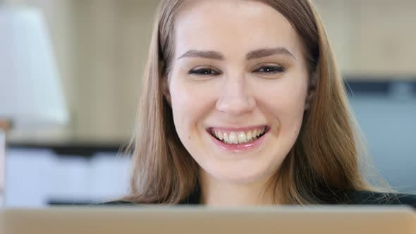 Cover Image for Woman Smiling Toward Camera while Working on Laptop