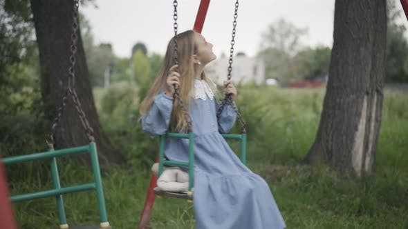 Thumbnail for Charming Cute Girl Swinging on Swings Outdoors
