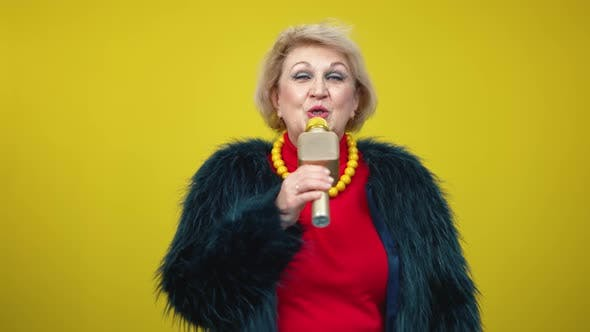 Thumbnail for Portrait of Elegant Senior Woman Singing on Microphone on Yellow Background
