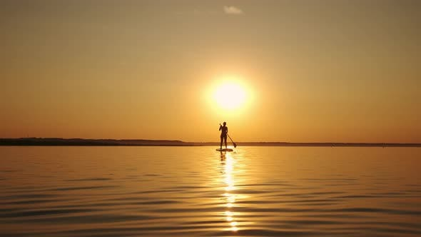 Woman Standing Firmly on Inflatable SUP Board and Paddling Through Shining Water Surface