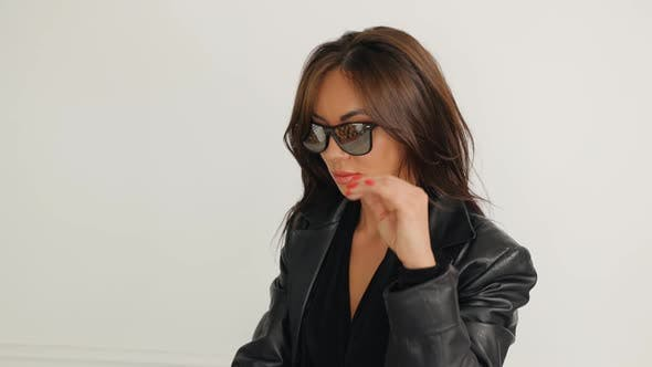 Young Woman Taking Off Sunglasses in Studio