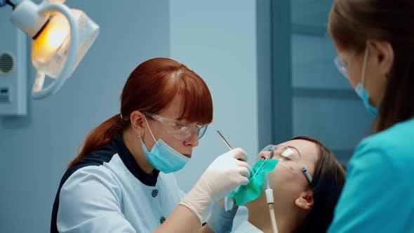 Thumbnail for Zahnarzt Frau heilt den Zahn des Patienten aufmerksam
