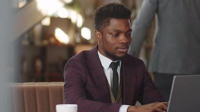 Portrait of Afro-American Businessman with Laptop in Restaurant