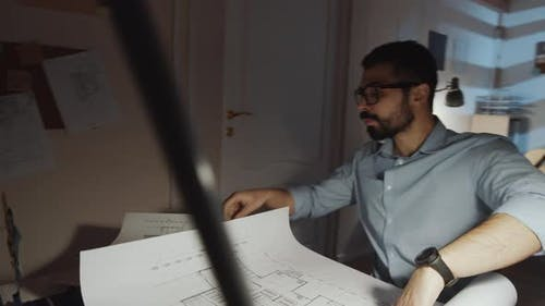 Architect Entering Office and Drawing Building Plan at Desk