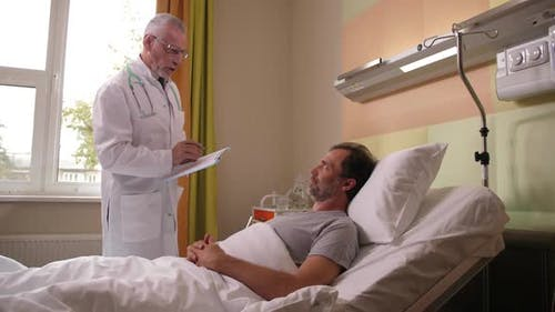 Doctor Visiting Recovering Patient in Clinic