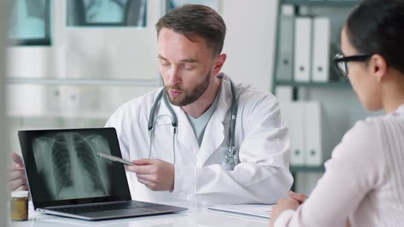 Thumbnail for Male Doctor Showing Lung X-Ray on Laptop to Woman during Consultation