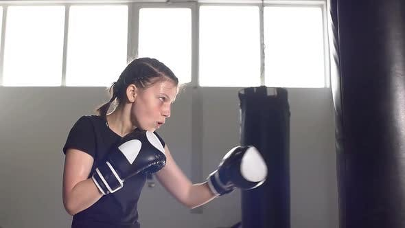 Thumbnail for Teen Girl in Boxing Gloves Is Working Out a Blow. Slow Motion