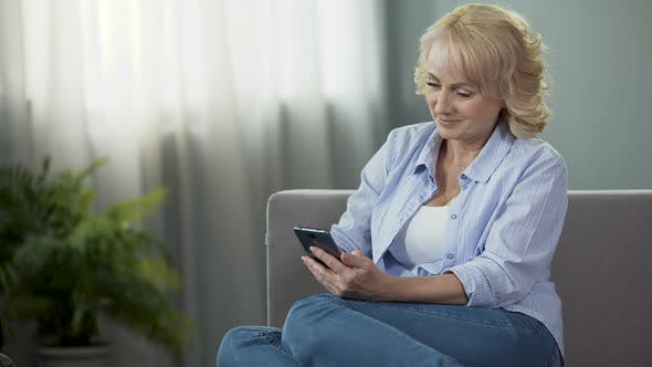 Thumbnail for Cheerful middle-aged female sitting on couch and viewing funny photos on phone