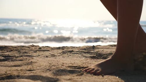 Close Up of Female Feet Walking on Golden Sand at the Beach with Ocean Waves at Background