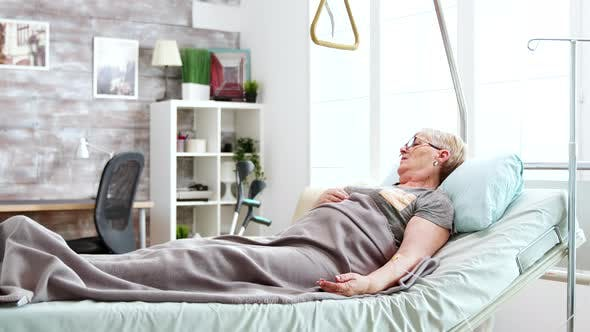 Thumbnail for Disabled Old Lady Lying in Hospital Bed in Bright and Cozy Nursing Home