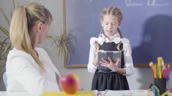 Thumbnail for Portrait of Charming Caucasian Girl in School Uniform Declaiming To Middle Aged Teacher Sitting