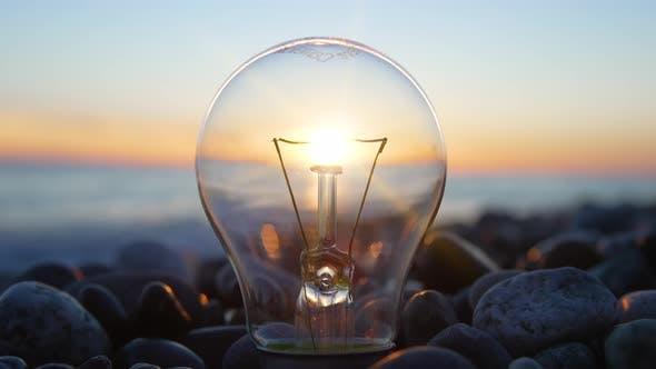 Light Bulb with Sunset Sky Background