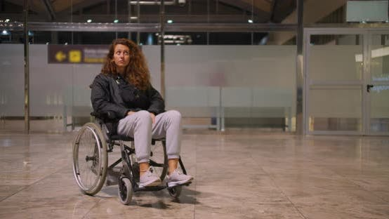 Cover Image for Young Disabled Woman in Wheelchair in an Airport. She Is Alone and Looking Around.