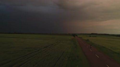 Aerial Dark Ominous Gray Storm Clouds On The Road Rides A Moped