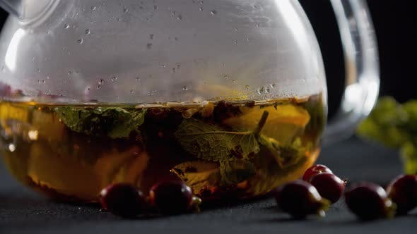 Close Up of a Teapot with Lemon, Tea and Herbs in the Water, Rosehip Near It,