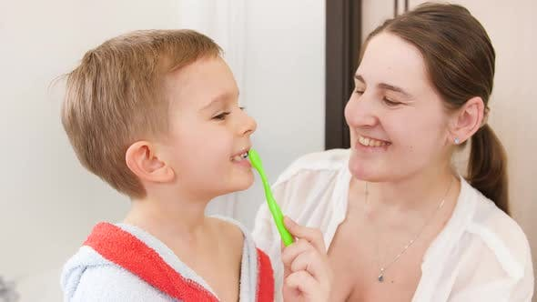 Portrait of Little Smiling Boy Brushing and Cleaning Teeth with His Smiling Mother in Bathroom