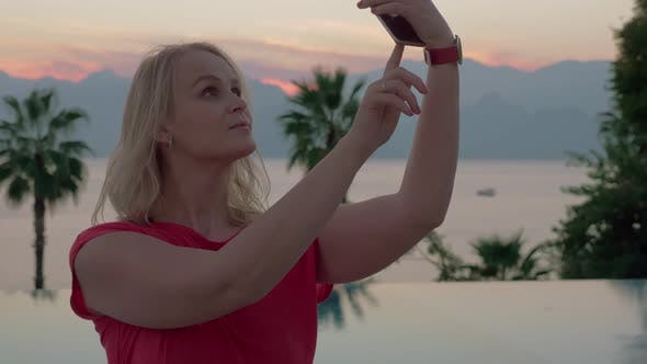 Thumbnail for A Young Woman Taking Selfies By the Beautiful Evening Scenery Near the Pool