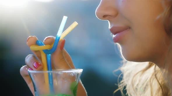 Thumbnail for Attraktive junge Frau trinkt einen Cocktail aus der Tube. Bei Sonnenuntergang scheint die Sonne in Ihrem Haar