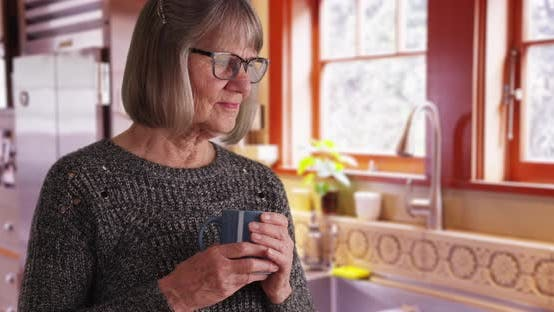 Aging woman with drink looking serious in domestic kitchen setting