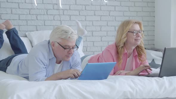 Portrait of Positive Caucasian Mid-adult Man and Woman in Eyeglasses Using Laptops and Smiling