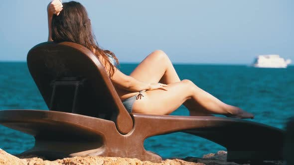 Thumbnail for Sexy Woman in a Swimsuit Is Lying on Sunbed on a Beach Against the Red Sea in Egypt.