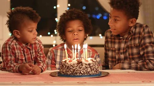 Boy Blows Out the Candles and Make a Wish.