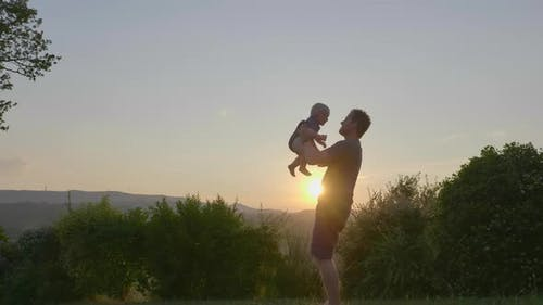 View of a Devoted Father Playfully Throwing His Curt Baby and Catching Him