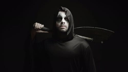 Grim Reaper Over Black Background with Axe in His Hands