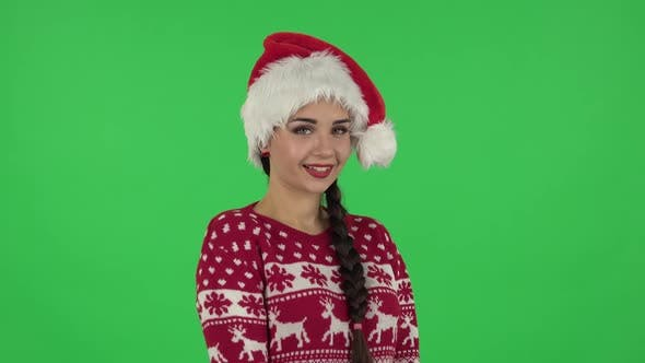 Portrait of Sweety Girl in Santa Claus Hat Is Smiling and Showing Heart with Fingers Then Blowing
