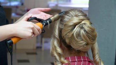 The Hairdresser Makes a Trendy Hairstyle on a Long Blond Hair