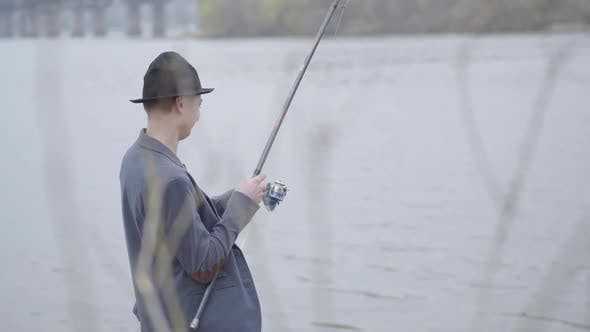 Thumbnail for Young Fisherman in a Jacket and a Cap with a Brim in the Early Morning Catch Fish