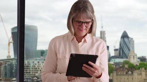 Joyful senior woman using handheld technology with view of cityscape behind her