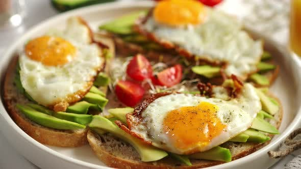 Thumbnail for Close Up of Healthy Breakfast with Sliced Avocado Sandwiches with Fried Egg