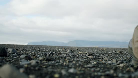 Thumbnail for A Close Up View of a Man Legs in Boots Walking on Black Sand and Stones on a Beach in Iceland