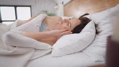 Beautiful Young Slim Caucasian Woman Sleeping in White Bed in the Morning