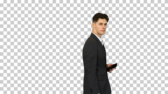 Thumbnail for Handsome suspicious businessman walking by with a phone in a
