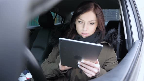 Woman Upset by Loss, while Using Tablet in Car