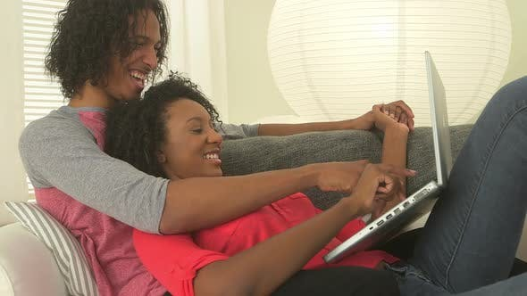Thumbnail for Black teen couple surfing the net on laptop