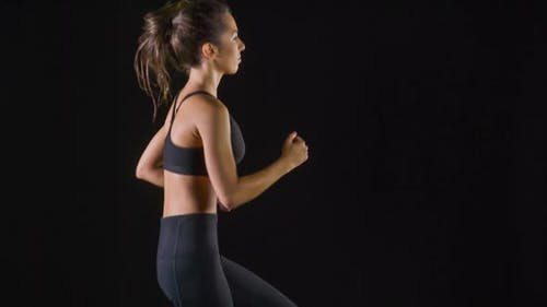 Athletic woman working out in front of a black background