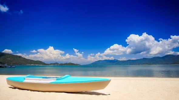 Blue White Metal Paddle Boat on Gold Sand By Azure Sea Beach