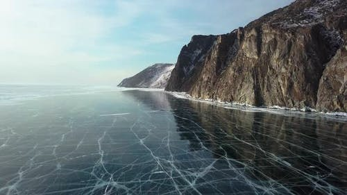 Ice with Cracks in Lake Baikal in Winter. Sagan-Zaba Cliff, Aerial View.