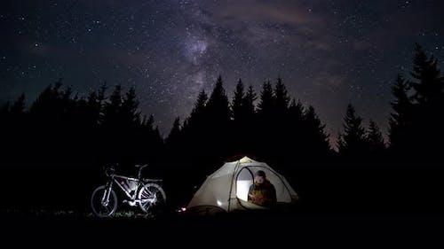A Man Reads a Book in a Tent
