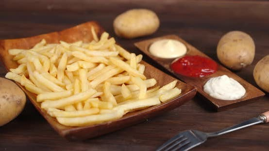 French Fries on a Wooden Plate with Variety of Sauces Rotates Slowly