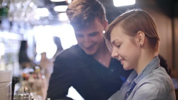Thumbnail for Woman and Man Looking at Mobile Phone at Bar