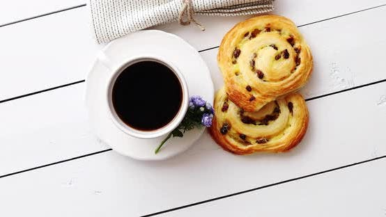 Thumbnail for Delicious Pastry with Raisins and a Cup of Coffee Top View.