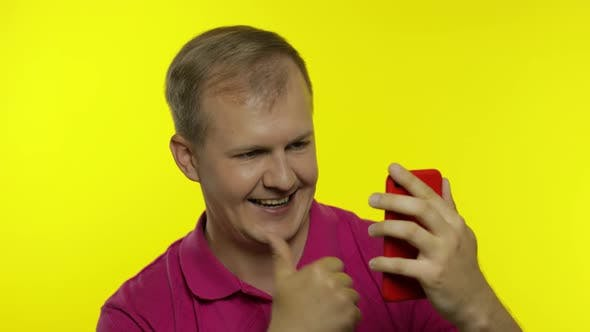 Thumbnail for Young Caucasian Man Posing in Pink T-shirt. Handsome Guy Using Mobile Phone and Win Something