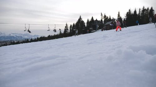 Snowboarder and Skiers Descends on Snow in Ski Resort. Unrecognizable Tourists Slides Down on Snowy